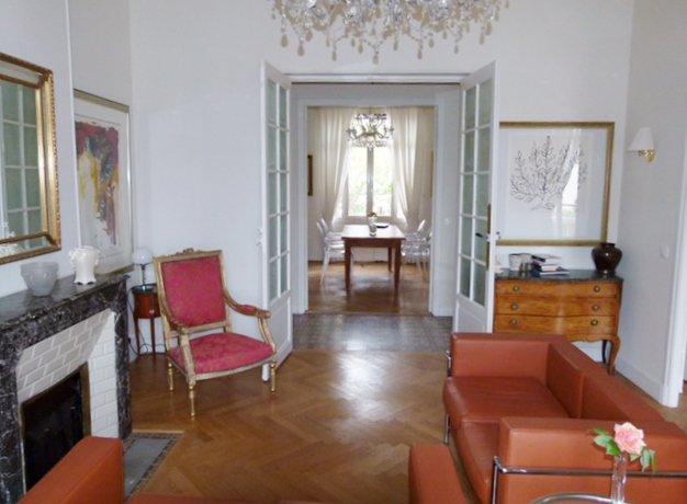 Séjour, chandelier, natural light, bay-window, wood floors, exposed bricks, fireplace