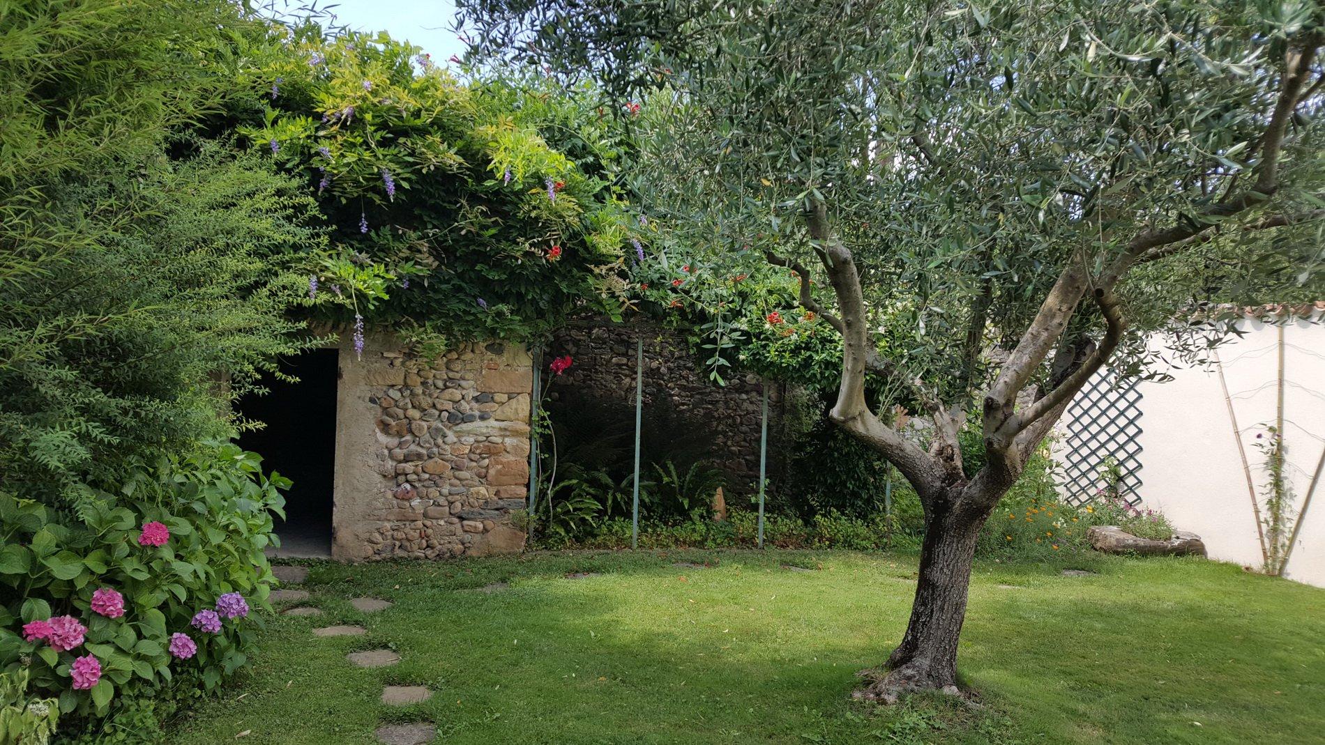 Vackert byhus med gård och anlagd trädgård