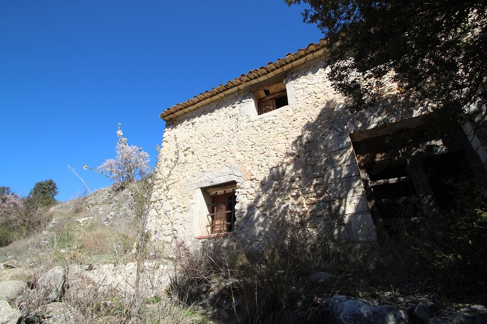 Ancien moulin en pierre dans un endroit naturel.