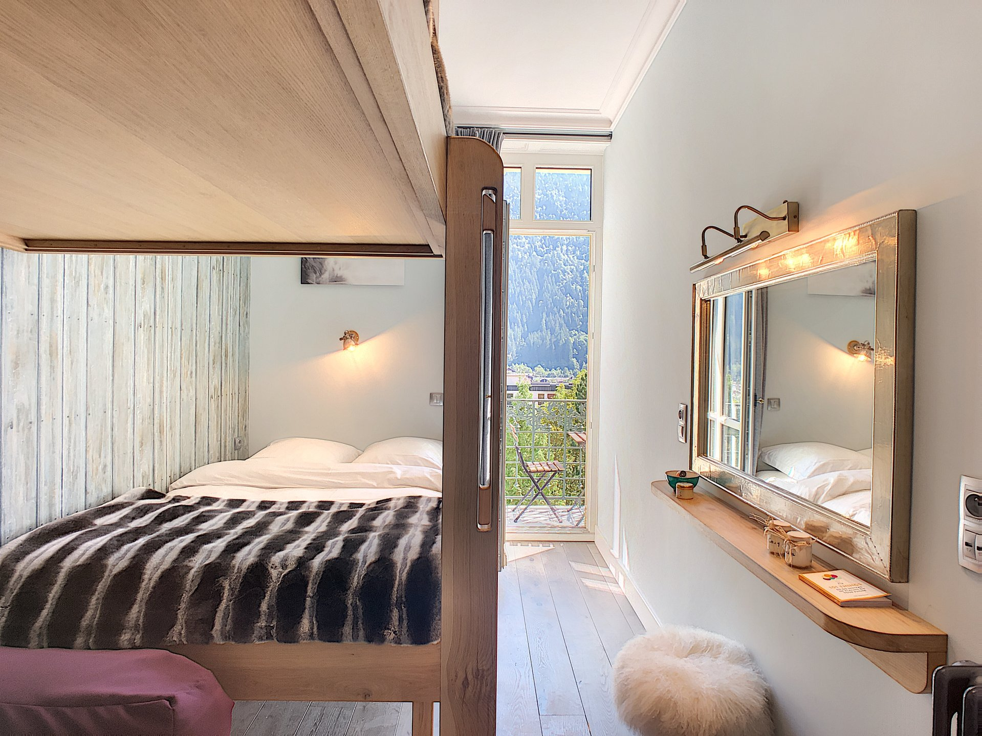 Bedroom with hand-crafted double bed plus bunk bed leading to south facing balcony