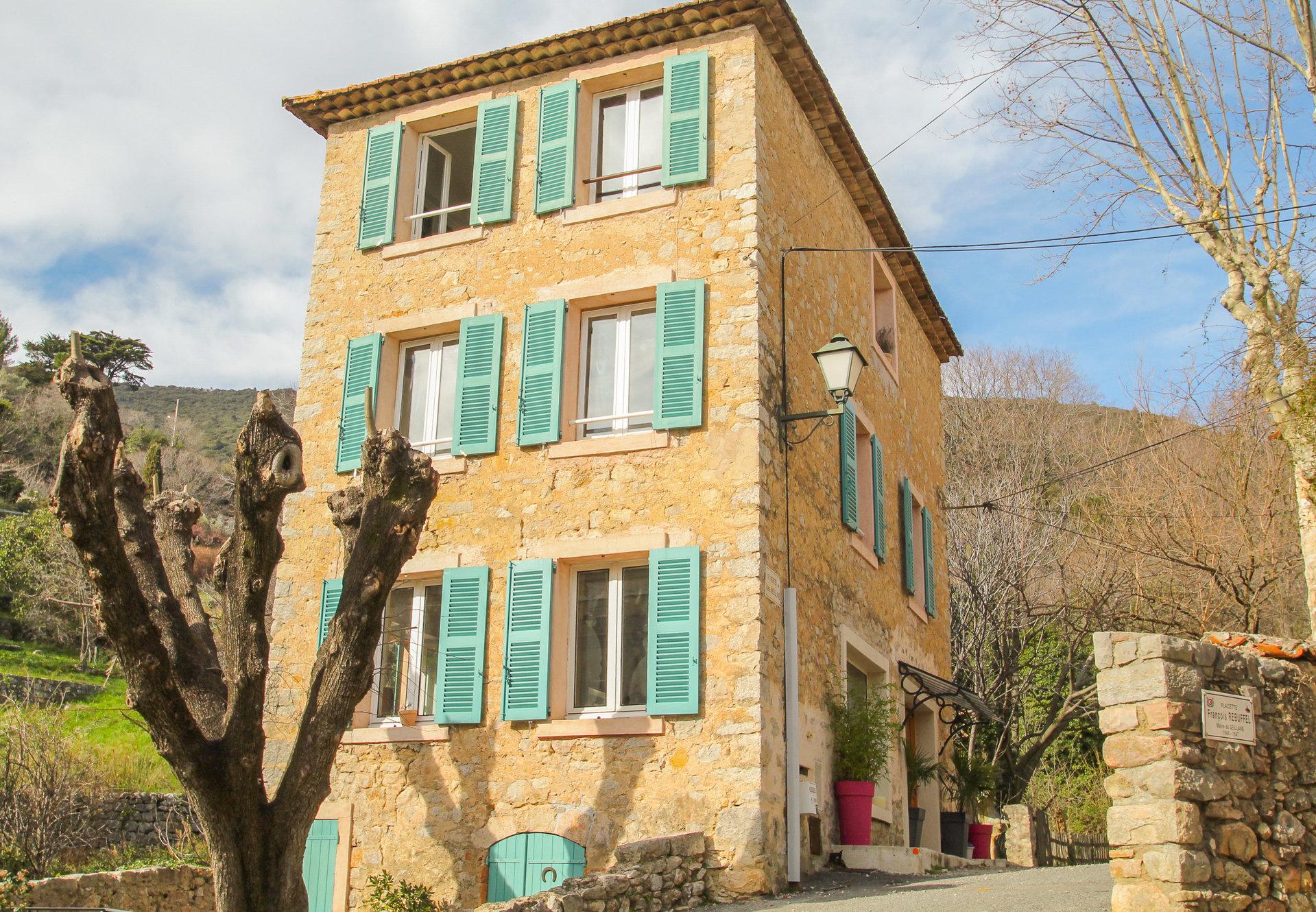 Maison de village en pierre située en bordure d'un ruisseau