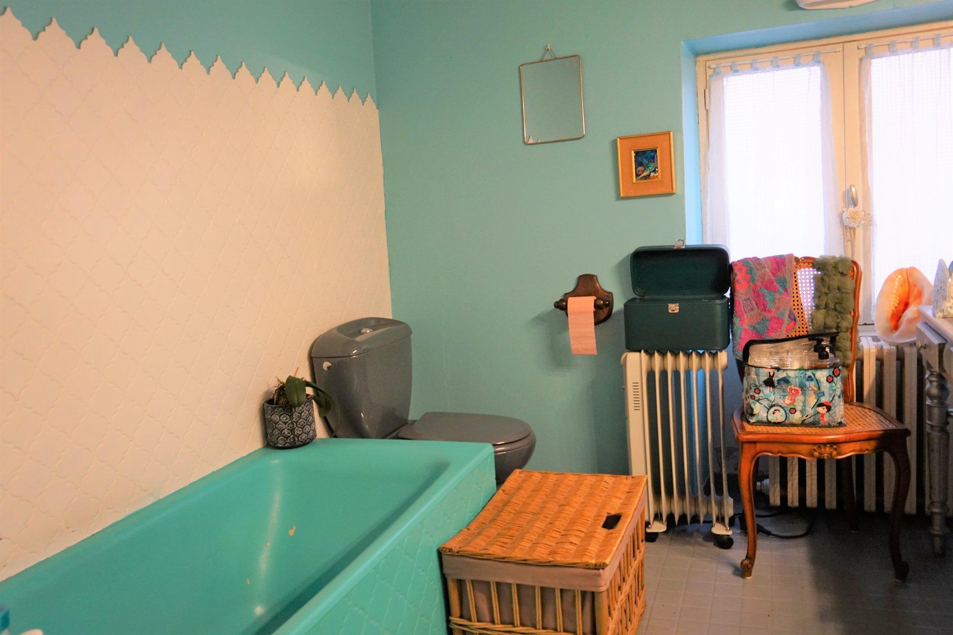Salle de bains avec baignoire et toilettes