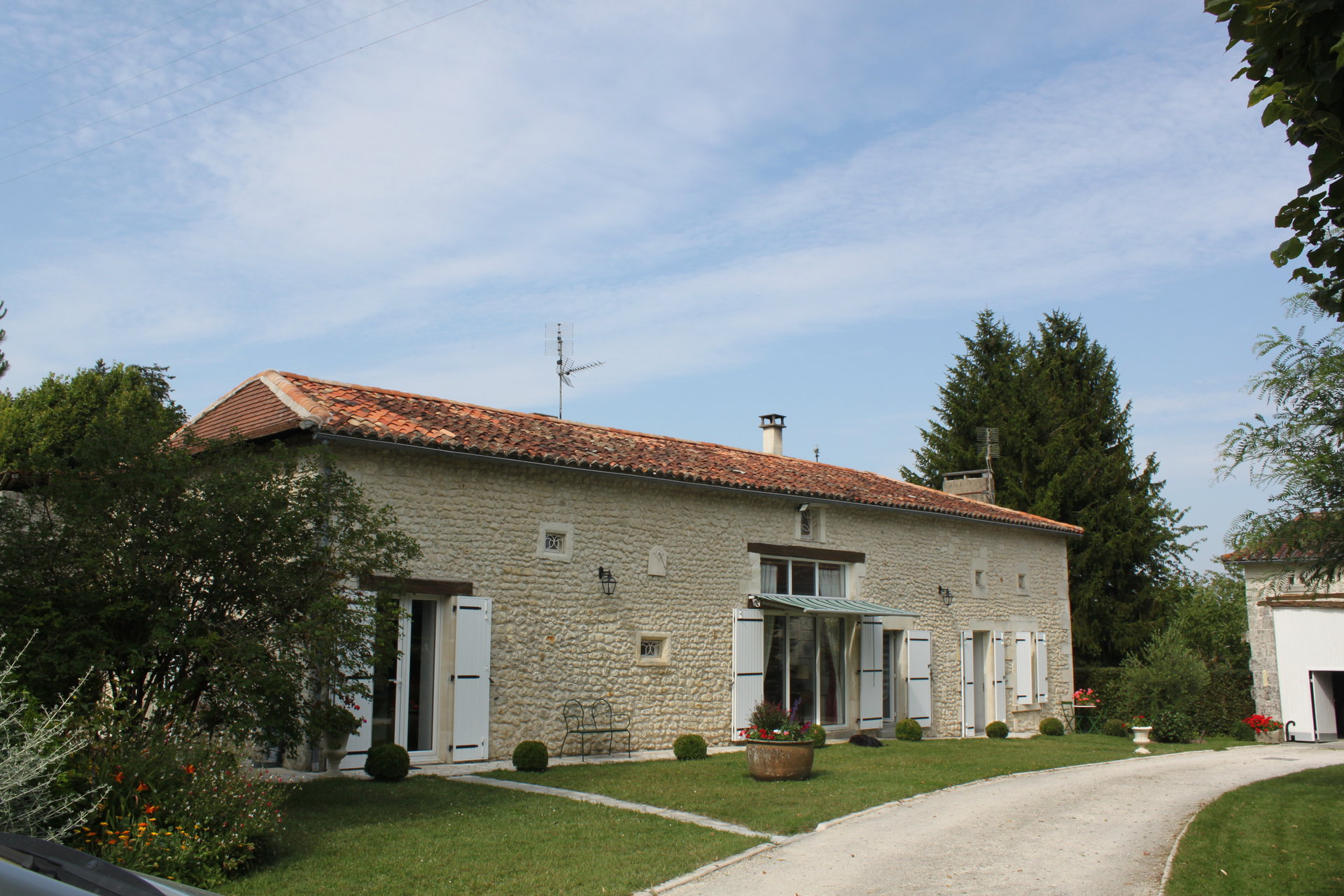A delightful longere style stone house set in pretty enclosed gardens with outbuildings