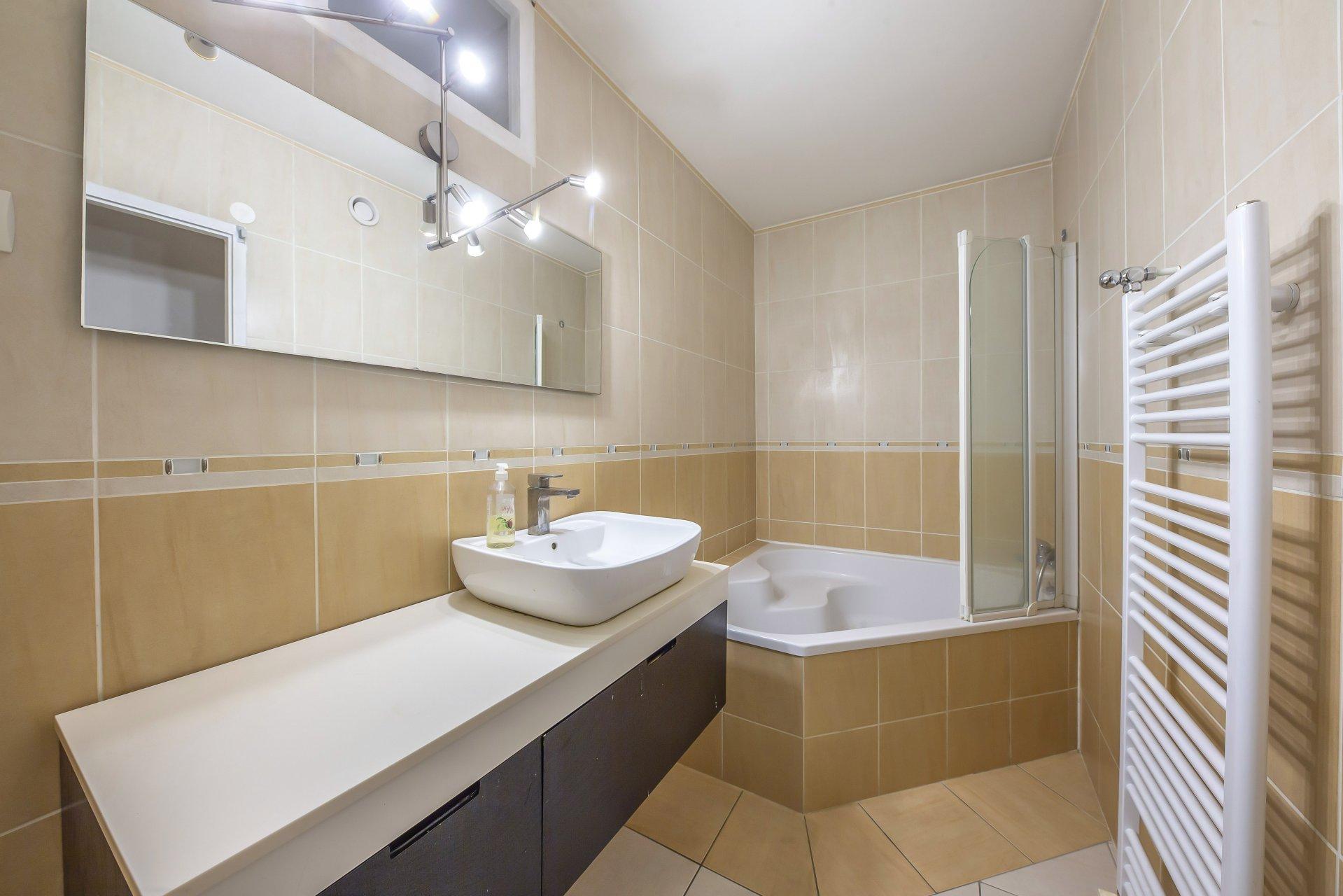La salle de bain avec baignoire et espace laverie