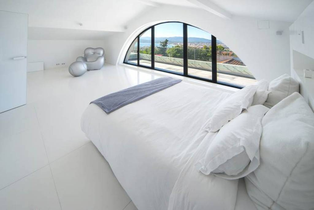 white bedroom with curved window
