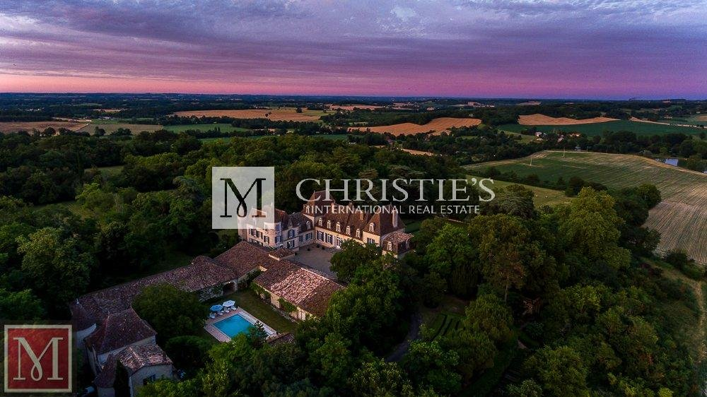 Ariel view of chateau surrounded by forest at sunset