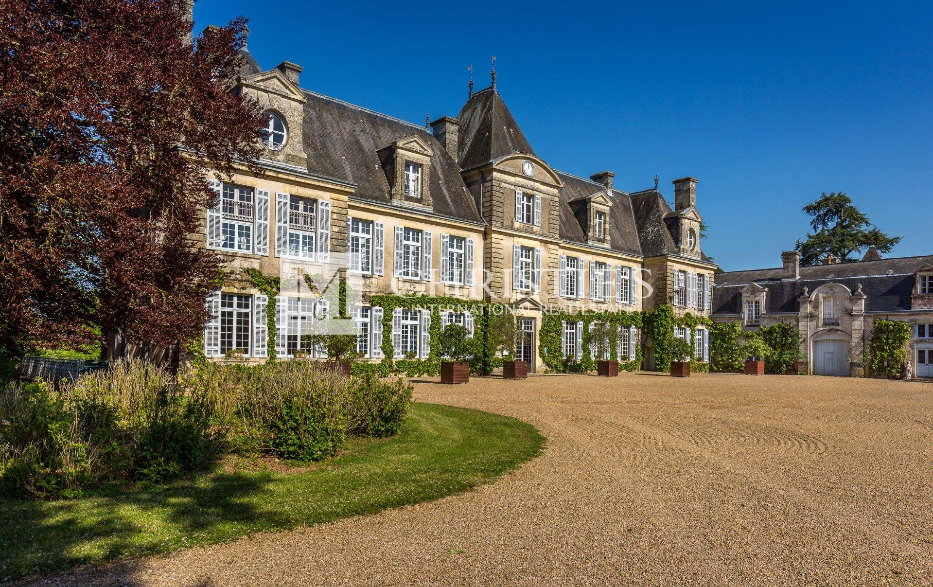 Large chateau with brown gravel driveway